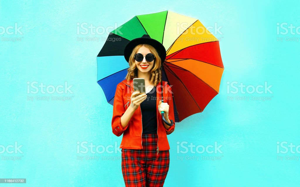 Portrait smiling young woman holding phone with colorful umbrella in...