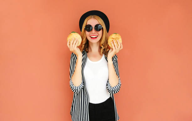 Portrait smiling young woman showing a burger wearing a black hat, sunglasses over wall background stock photo