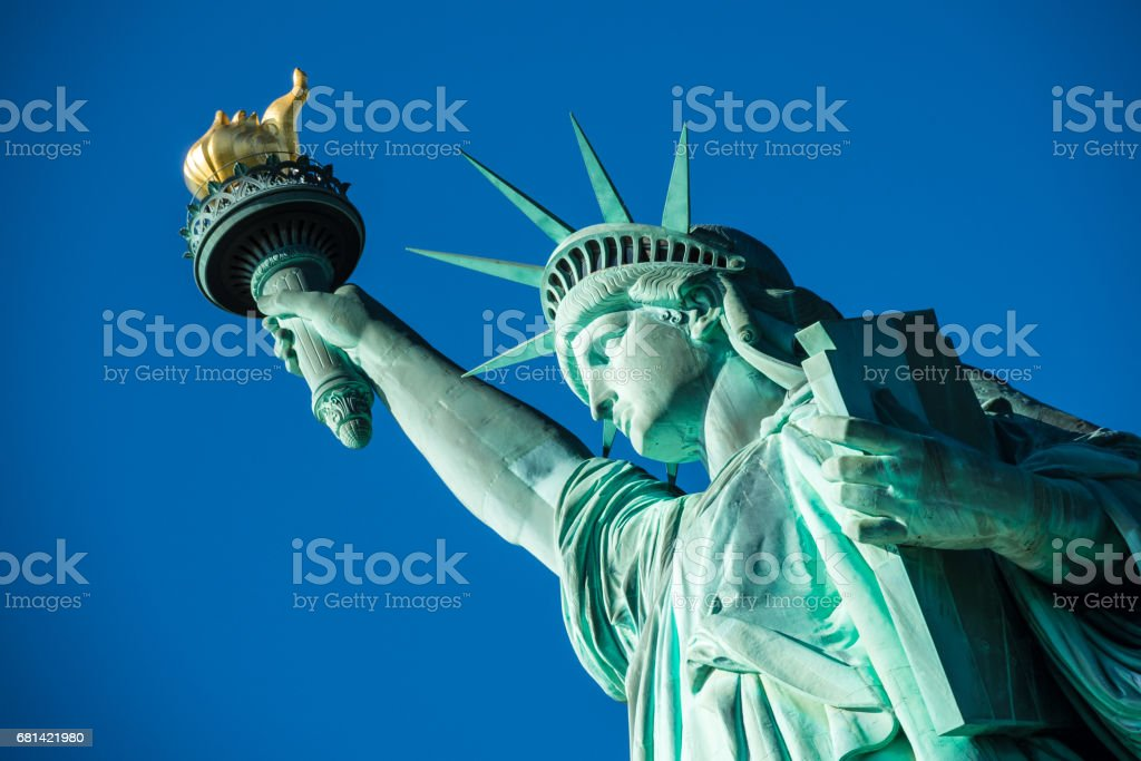 Portrait Statue of Liberty at perfect weather conditions blue sky copper torch stock photo