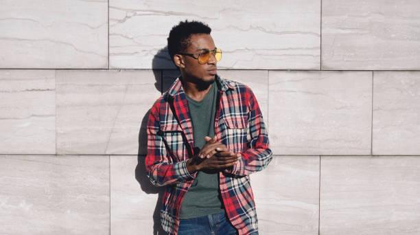 porträt stilvoll afrikanischer mann trägt rotes plaides hemd, wegschauen, kerl posiert auf der stadtstraße, grauer backstein-hintergrund - vogue muster stock-fotos und bilder