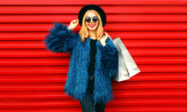 Portrait stylish smiling woman with shopping bags wearing blue faux fur coat, black round hat and sunglasses posing over red wall background stock photo