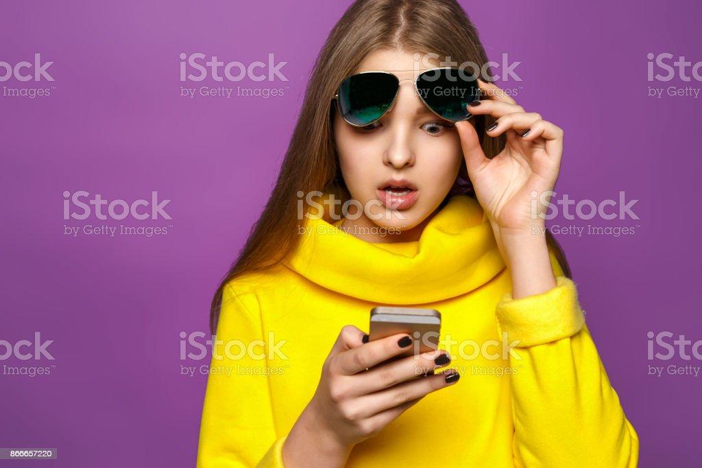 Joven sorprendida retrato de mensaje en smartphone en el suéter amarillo brillantes, aislar sobre un fondo violeta - foto de stock