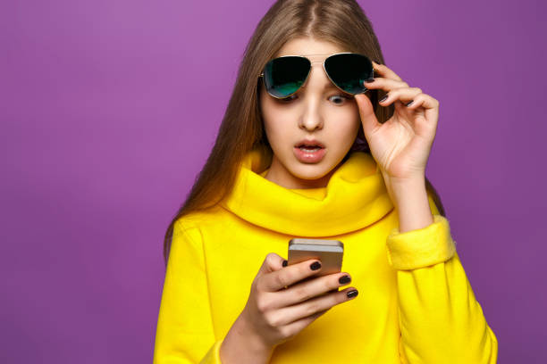 portrait surprised young girl from message on smartphone in brightly yellow sweater, isolate on a violet background - astonishment stock photos and pictures