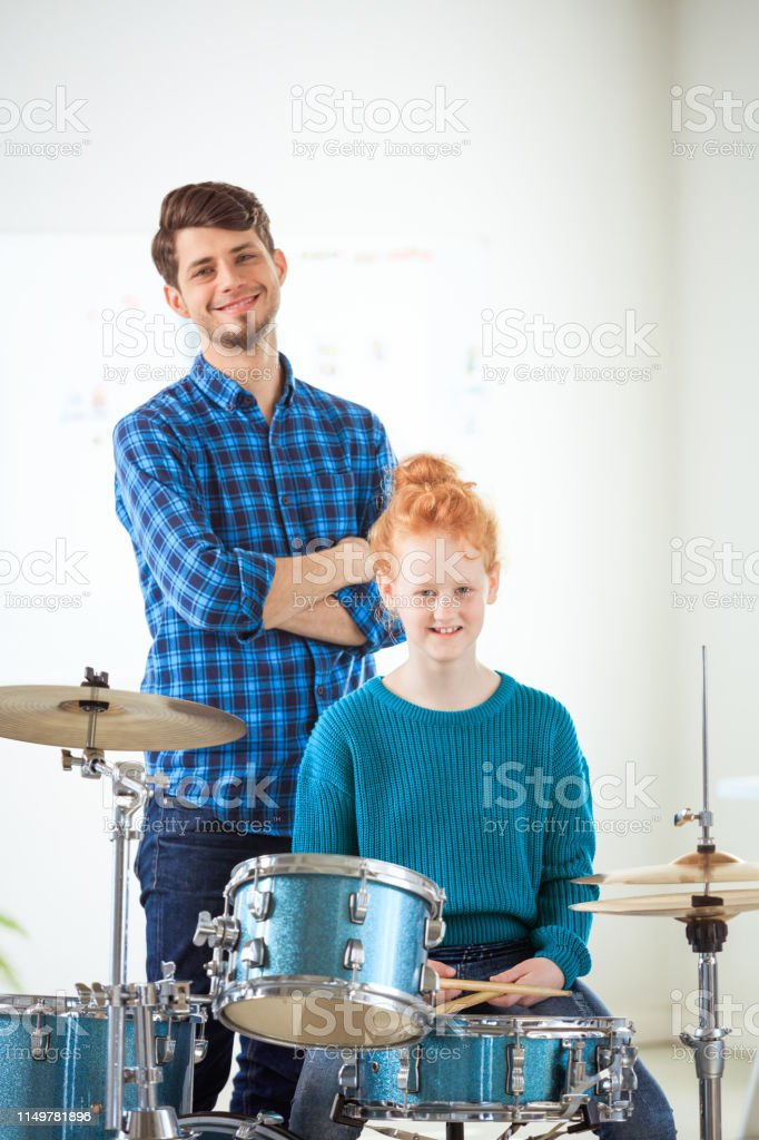 Portrait teacher and drummer in classroom Portrait of confident teacher and drummer in classroom. Smiling female student is with instructor in training class. They are at conservatory. 12-13 Years Stock Photo
