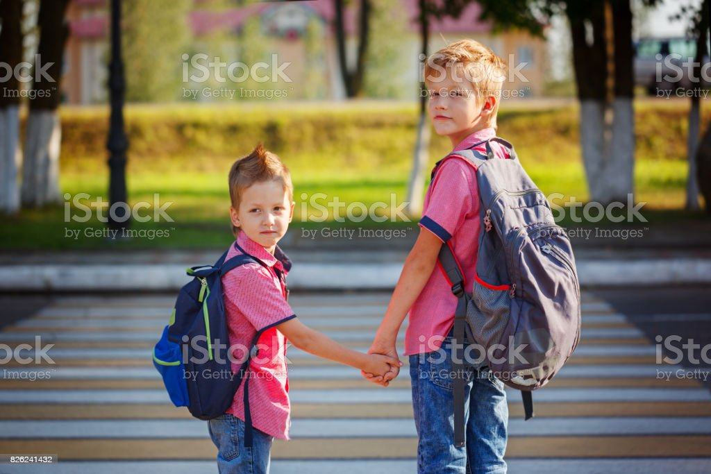 Portrait two adorable boys with backpack near pedestrian crossin stock photo