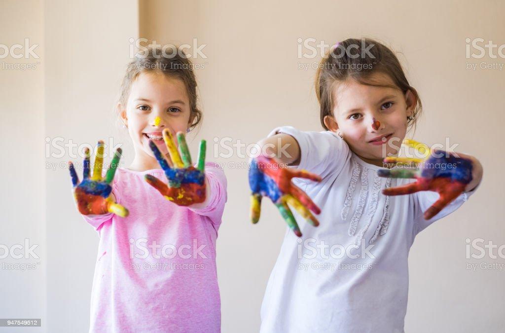 694aa4718daef Porträt von zwei süße Schwestern mit Multi farbige Hände Lizenzfreies  stock-foto