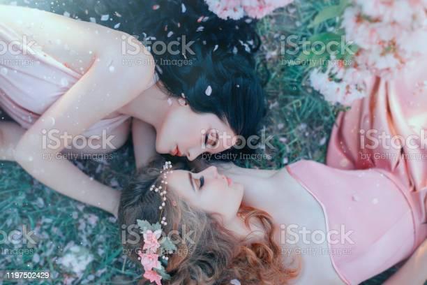 Portrait two young women lie cuddling on grass in spring garden long picture id1197502429?b=1&k=6&m=1197502429&s=612x612&h=lkq8tsrkzom4 b88pfi gxharmtxxcdcic5ajvhszme=