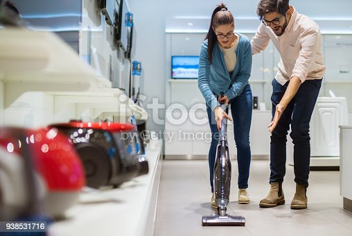 istock Portrait view of cute excited charming young hardworking student girl with eyeglasses holding vacuum cleaner while her boyfriend standing next to her amazed in a tech store. 938531716