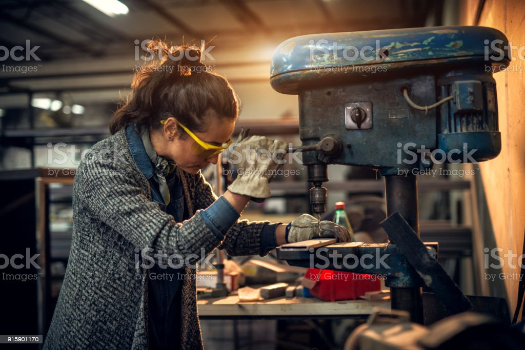 Portrait view of focused serious middle aged professional female carpentry working with an electric drill in the workshop. stock photo