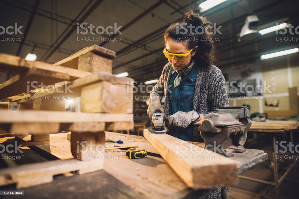 Portrait view of hardworking middle aged professional female carpenter worker working with sandpaper and choosing wood in the workshop. Portrait view of hardworking middle aged professional female carpenter worker working with sandpaper and choosing wood in the workshop. Adult Stock Photo