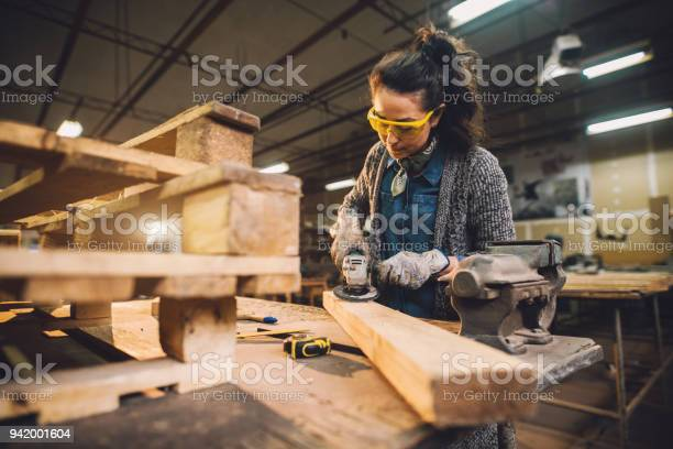 Portrait View Of Hardworking Middle Aged Professional Female Carpenter Worker Working With Sandpaper And Choosing Wood In The Workshop Stock Photo - Download Image Now