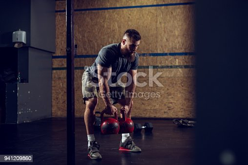 944655208 istock photo Portrait view of young bearded focused strong muscular shape bodybuilder man crouching with heavy kettlebells in hands at the gym. 941209860