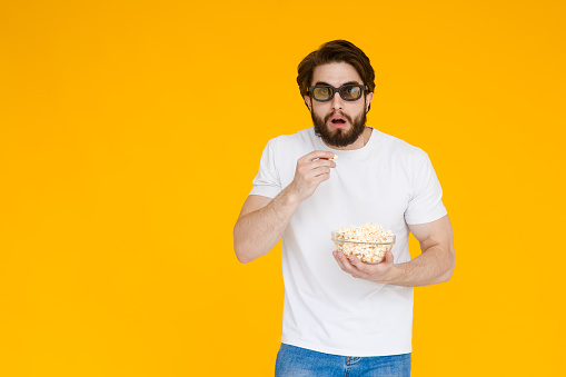Portrait vogue young man in 3d glasses, white t-shirt watching movie film, holding popcorn, cup of soda isolated on bright yellow background. People sincere emotions lifestyle concept.