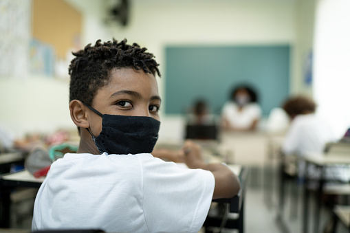 Portrait wearing face mask of a schoolboy studying in the classroom