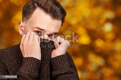 portrait White young guy hiding his face in sweater. Portrait of a man on autumn background with bokeh.