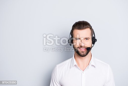 istock Portrait with copy space, empty place for advertisement of stylish, cheerful, harsh, virile operator having headset with microphone on head looking at camera isolated on grey background 970425350