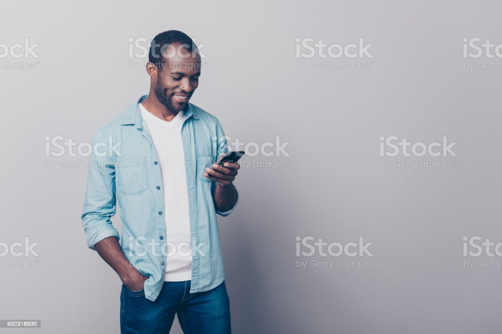 Portrait with copy space, empty place of cheerful guy in jeans, shirt having smart phone, holding arm in pocket of pants, texting sms, checking email, searching contact, using wifi, 5G internet stock photo