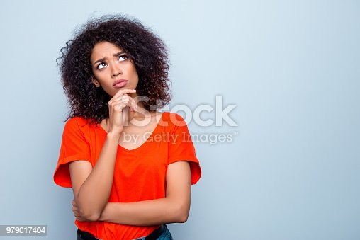 istock Portrait with copy space empty place of thoughtful minded woman with modern hairdo holding hand on chin looking up trying to find solution isolated on grey background 979017404
