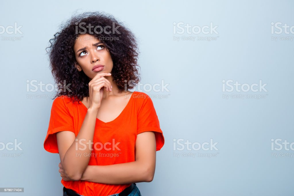 Portrait with copy space empty place of thoughtful minded woman with modern hairdo holding hand on chin looking up trying to find solution isolated on grey background stock photo