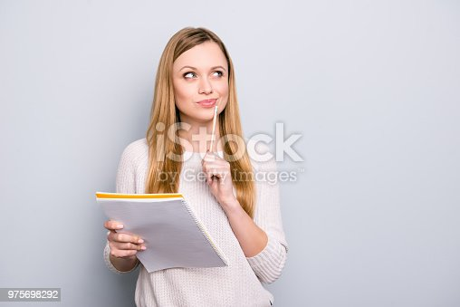 istock Portrait with copy space empty place of thoughtful pensive girl having copybook and pen in hands looking up, writer waiting for muse, isolated on grey background 975698292