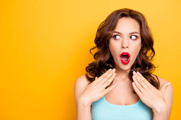 portrait with copy space for advertisement of shocked afraid woman looking with eyes at empty place having wide open mouth eyes gesturing palms isolated on yellow background - astonishment stock photos and pictures