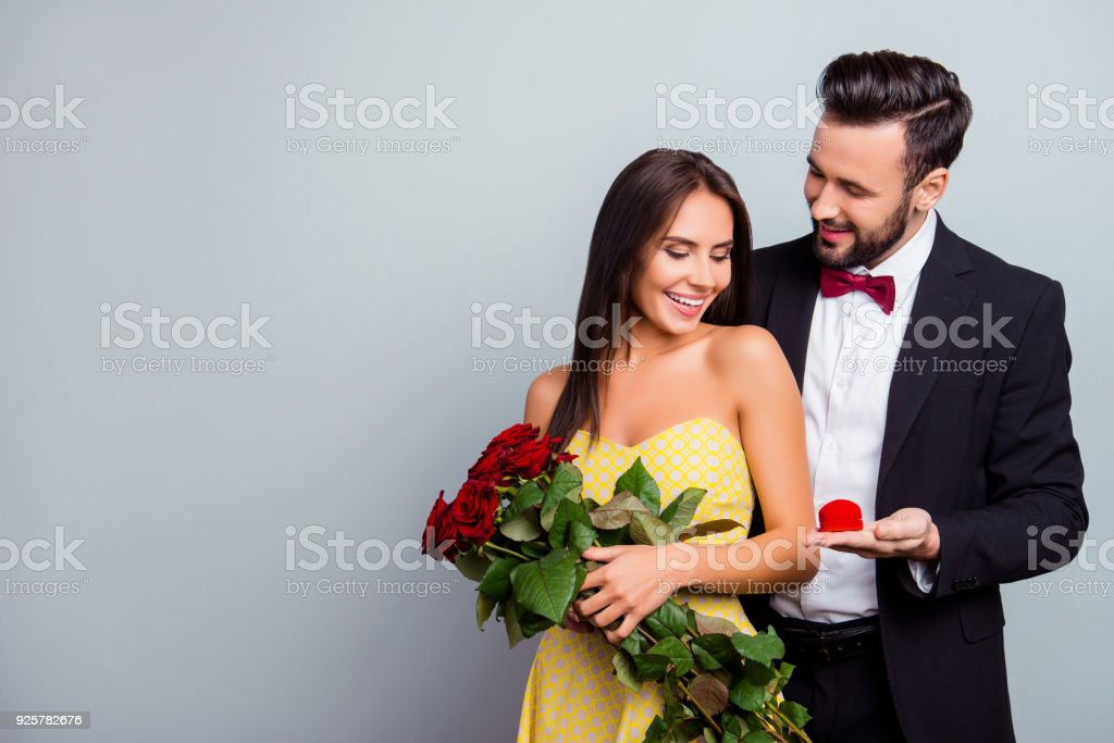 Portrait with copy space of attractive family, couple in formal wear, sexy wife in dress holding bouquet of red roses, husband in tuxedo embracing her from back side and presenting a case with ring стоковое фото