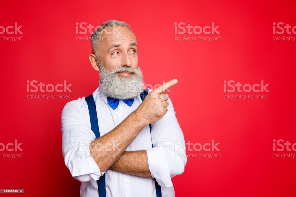 Portrait avec l'espace de la copie de l'esprit, méditer, styliste professionnelle, rétro, coiffeur avec noeud papillon bleu et bretelles pointant sur la place vide, produit avec l'index, isolé sur un fond rouge - Photo