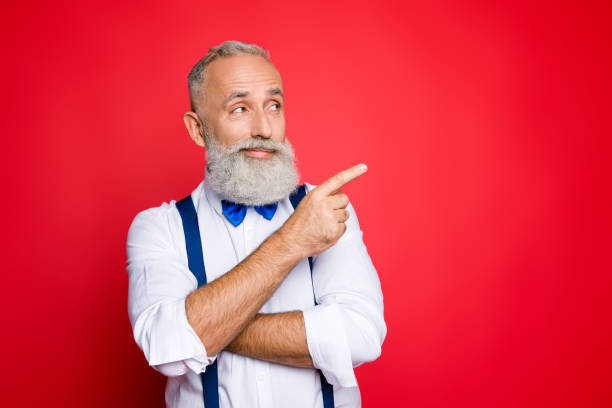 Portrait with copy space of minded, ponder, professional, retro stylist, barber with blue bowtie and suspenders pointing on empty place, product with forefinger, isolated on red background Portrait with copy space of minded, ponder, professional, retro stylist, barber with blue bowtie and suspenders pointing on empty place, product with forefinger, isolated on red background suspenders stock pictures, royalty-free photos & images