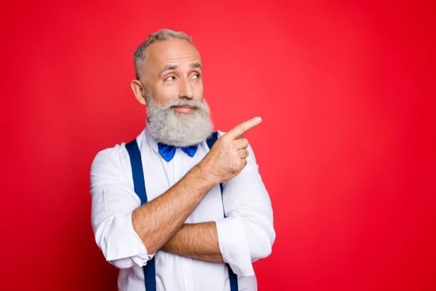 portre ile kopya yer-in fikirli, düşünmek, profesyonel, retro stilist, mavi papyon ve boş yere, ürün kırmızı zemin üzerine izole işaret parmağı ile işaret askısı ile berber - pantolon askısı stok fotoğraflar ve resimler