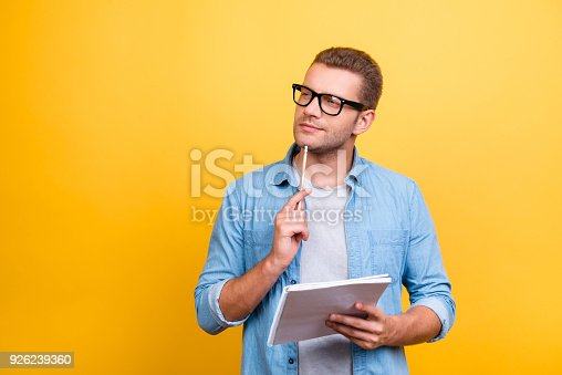 926239360 istock photo Portrait with copy space of thoughtful, serious, bearded man in spectacles holding copybook and touching chin with pen with thoughtful expression over grey background 926239360