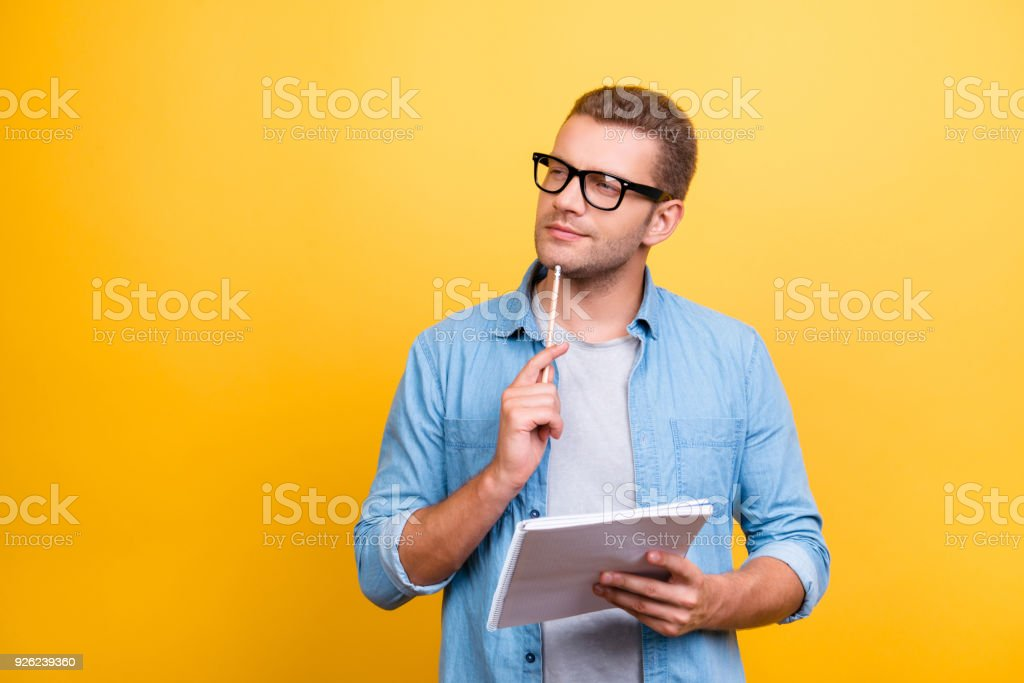Portrait with copy space of thoughtful, serious, bearded man in spectacles holding copybook and touching chin with pen with thoughtful expression over grey background stock photo