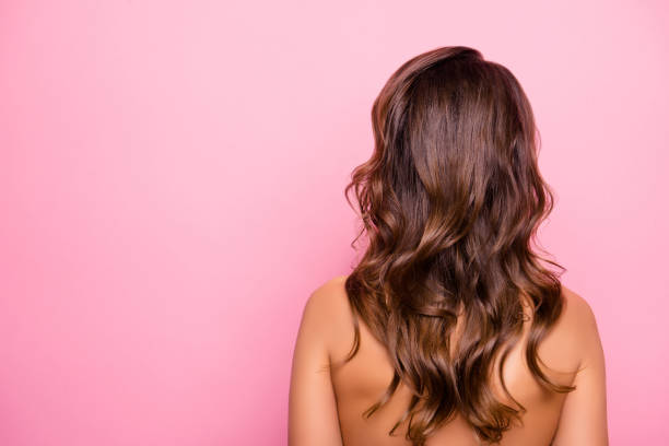 portrait with copy space, rear view of young, sexy, pretty, attractive, naked, shirtless girl with curly, perfect, ideal hair, isolated on pink background - capelli castani foto e immagini stock