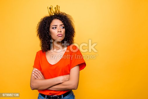 istock Portrait with copy-space empty place for advertisement of proud arrogant woman with modern hairdo holding arms crossed looking at empty place with offensive expression isolated on yellow background 979982106
