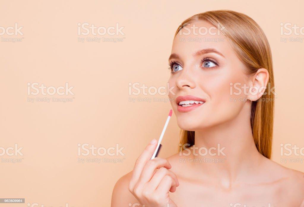 Retrato com copyspace vazia Coloque para produto de menina alegre bonito, charmoso, testando novo batom isolada em fundo bege, perfeição, conceito de anúncio de bem-estar - Foto de stock de Adulto royalty-free