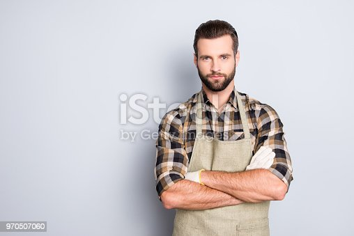 Portrait with copyspace, empty place of attractive, virile, harsh farmer with stubble in uniform having his arms crossed, looking at camera isolated on grey background, advertisement concept