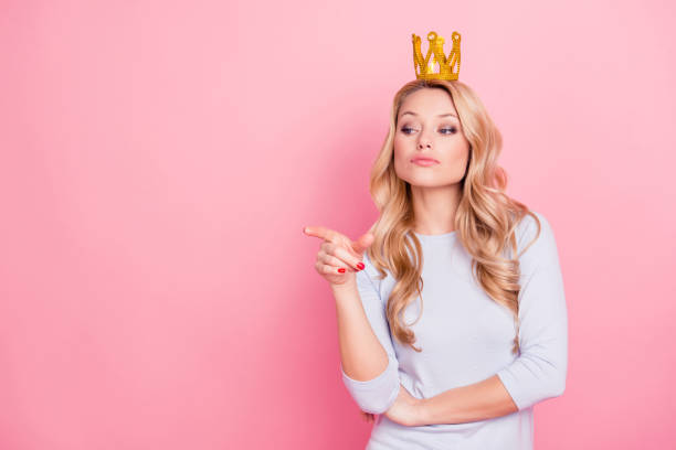 portrait with copyspace empty place of confident proud arrogant woman with gold crown on her head pointing forefinger, miss i want, isolated on pink background - arrogance stock pictures, royalty-free photos & images