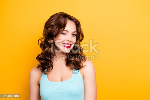 Portrait with copyspace empty place of foxy funny girl with modern hairdo winking with one eye having beaming smile red pomade lipstick isolated on yellow background