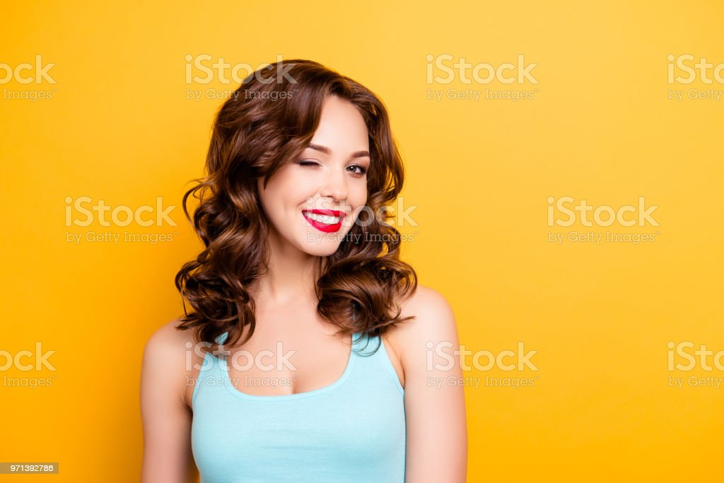 Portrait with copyspace empty place of foxy funny girl with modern hairdo winking with one eye having beaming smile red pomade lipstick isolated on yellow background stock photo