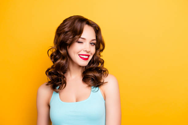 portrait with copyspace empty place of foxy funny girl with modern hairdo winking with one eye having beaming smile red pomade lipstick isolated on yellow background - blinking stock pictures, royalty-free photos & images