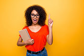 istock Portrait with copyspace of impressed astonished girl in eyewear pointing forefinger up find great good idea holding notepad in hand isolated on yellow background 979960478