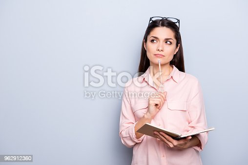 istock Portrait with copyspace of thoughtful concentrated busy charming woman having notepad and pen in hands planning, expertising, analyzing isolated on grey background, advertisement concept 962912360