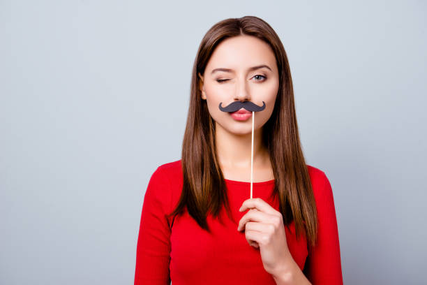portrait with empty copy space for text of cool pretty charming crazy girl holding black paper party mustache on stick, winking with pout lips, standing over gray background - mask disguise stock photos and pictures