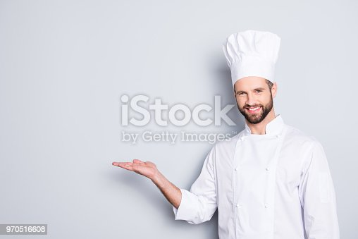 istock Portrait with empty place for advertisement, product of joyful attractive chef cook in beret with stubble holding copy space on his palm, looking at camera, isolated on grey background 970516608