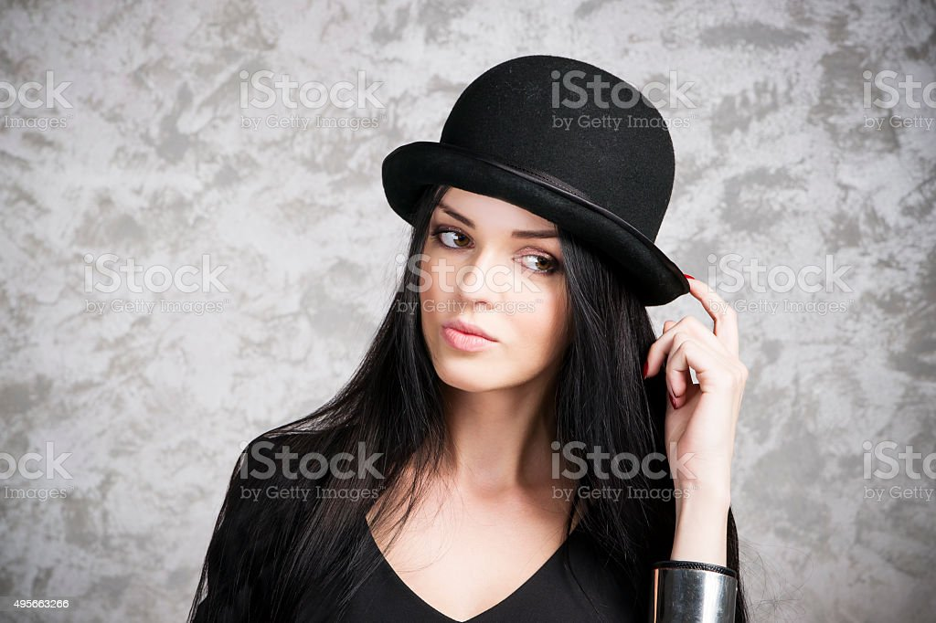 Portrait woman in a black dress and bowler hat royalty-free stock photo 701eb073e445