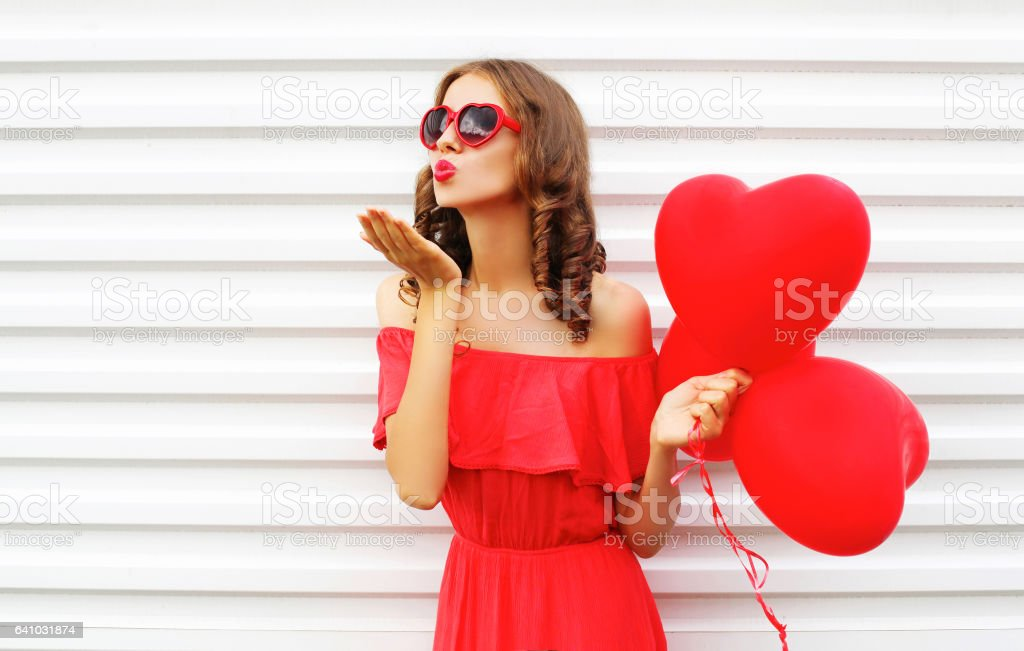 Portrait woman in red dress sends air kiss with balloon heart shape over white background stock photo