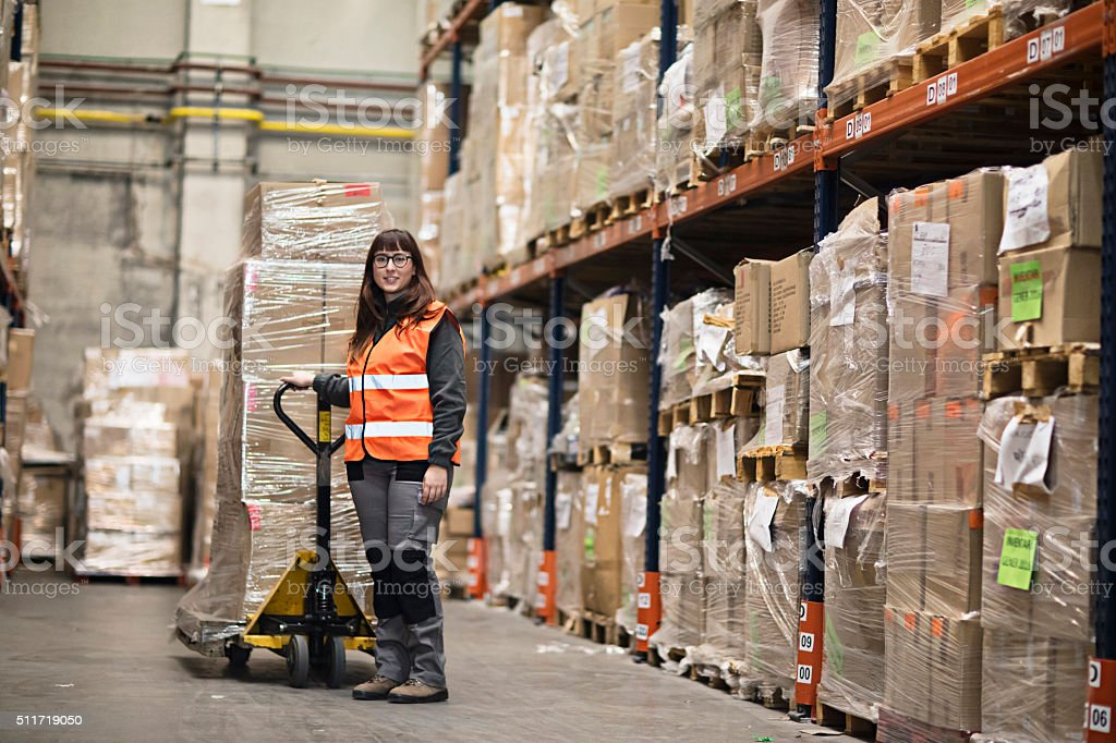 Portrait woman moving boxes in a warehouse stock photo