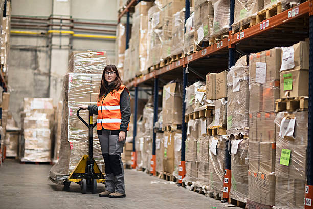Portrait woman moving boxes in a warehouse Portrait of a young woman moving boxes in a warehouse. pallet jack stock pictures, royalty-free photos & images