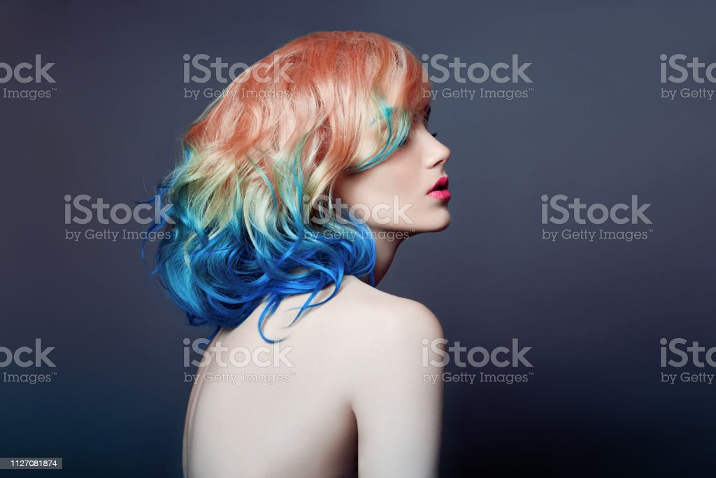 Portrait woman with bright colored flying hair, all shades purple blue. Hair coloring, beautiful lips and makeup. Hair fluttering in wind. Sexy girl with short  hair. Professional creative coloring - Foto stock royalty-free di Accudire