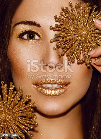 455111881 istock photo Portrait woman with Christmas decorations snowflakes. Fashion gold make-up. 496381440