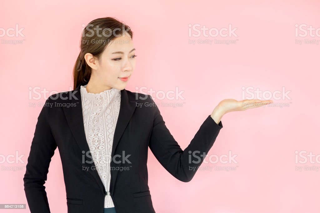 Portrait young Asian beautiful businesswoman, confident looking on pink background, present posing royalty-free stock photo